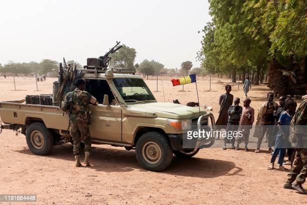 Soldiers of the Chad Army stand next to a Land Cruiser while bystanders look on before buing sheep at the Koundoul market 25 km from N'Djamena on...