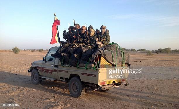 Soldiers of the Chadian hold a Chadian national flag as they patrol in armoured vehicles on January 21 at the border between Nigeria and Cameroon...