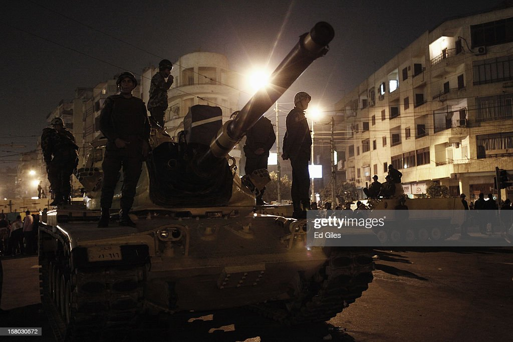 Soldiers of the Egyptian Republican Guard stand on a tank parked by the outer walls of Egypt's Presidential Palace, during a demonstration against Egyptian President Mohammed Morsi on December 9, 2012 in Cairo, Egypt. Anti-Morsi protesters continue to demonstrate across Egypt against the country's draft constitution, rushed through parliament in an overnight session on November 29. The country's new draft constitution, passed by a constitutional assembly dominated by Islamists, will go to a referendum on December 15. (Photo by Ed Giles/Getty Images).