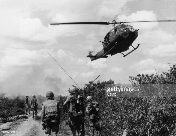 """Soldiers of the fourth U.S. Marine Regiment patrol the demilitarized zone in Vietnam as a Marine Corps """"Huey"""" helicopter passes overhead, Vietnam..."""