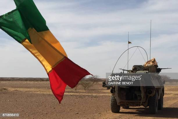 Soldiers of the France's Barkhane mission patrol in a military vehicle next to a Malian national flag on November 2 2017 in central Mali in the...