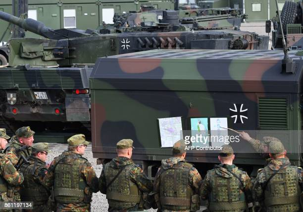 Soldiers of the German armed forces Bundeswehr receive a command output in a camp during the informative educational practice Land Operation Exercise...