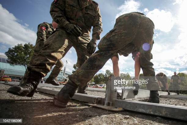Soldiers of the German Armed Forces set up a tent to accomodate additional folding beds in front of a new emergency shelter for migrants at the...