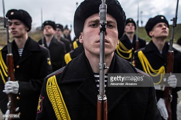 Soldiers of the honor guard prepare to march as people celebrate the first anniversary of the signing of the decree on the annexation of the Crimea...
