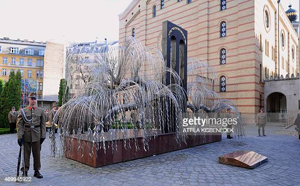 Soldiers of the honour guard stand beside the 'Emanuel Memorial tree' in the Raoul Wallenberg Memorial garden of Budapest synagogue on April 16 2015...