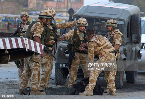 Soldiers of the International Security Assistance Force carry a dead body at the scene of a second apparent suicide car bomb in Kabul14 November 2005...