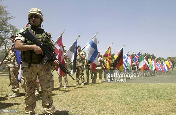 Soldiers of the International Security Assistance Force display their country's flags as an Italian soldier stands guard during a change of command...