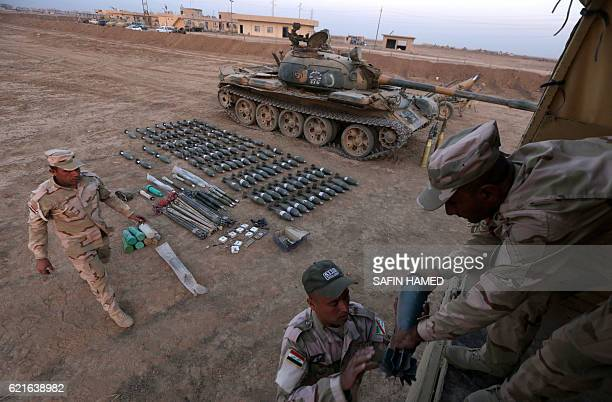 Soldiers of the Iraqi army display on November 7 weapons confiscated from the Islamic State group jihadists in the town of Qaraqosh 30 kms east of...