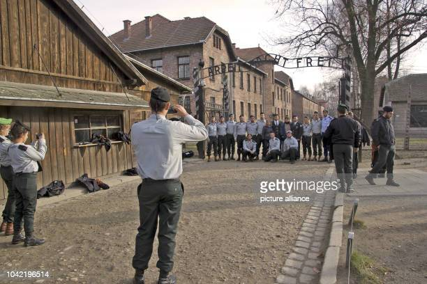Soldiers of the Israeli army take photographs below the famous gate which displays the motto 'Arbeit macht frei' lit Work brings freedom' at...