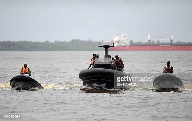 Soldiers of the Ivorian navy commandos steer speedboats newly purchased by Ivorian navy from France at Abidjan military base on June 23 before the...