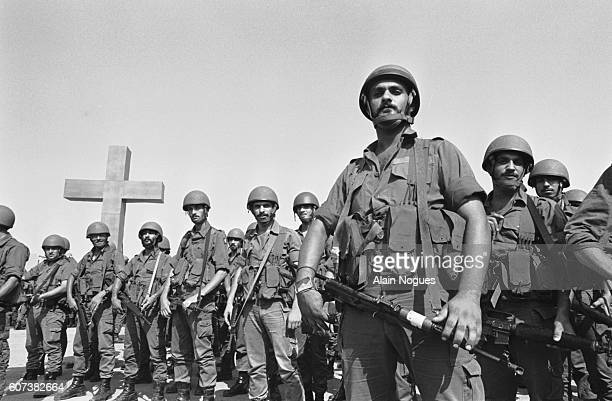 Soldiers of the Kataeb phalanx pose in front of a large crucifix. | Location: Lebanon.