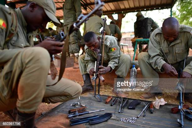 Soldiers of the Malian Armed Forces clean their AK47 rifle after shooting with live ammunition at the shooting range at a training base on March 09...