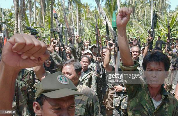 Soldiers of the Moro Islamic Liberation Front cheer at the Islamic Center in Buliok on March 28 2004 on the southern island of Mindanao Philippines...