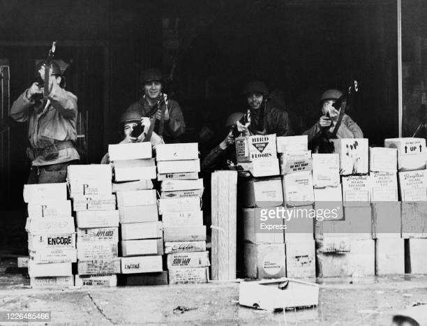 Soldiers of the National Guard shelter behind a stack of boxes during the race riots in Newark, New Jersey, in July 1967. The riots were sparked by...