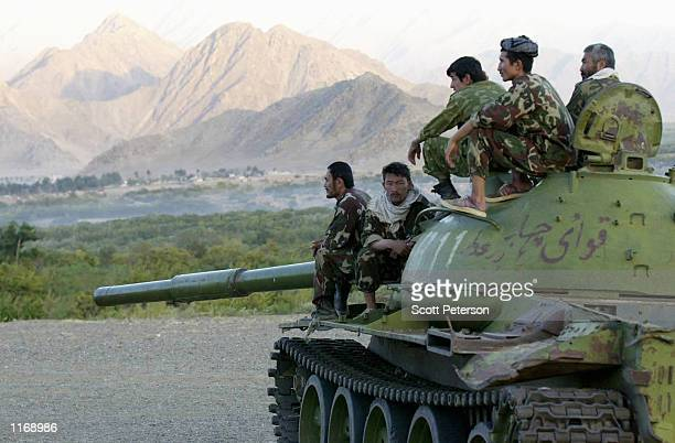 Soldiers of the opposition Northern Alliance sit on a tank at sunset October 6 2001 in Jabal Saraj Afghanistan
