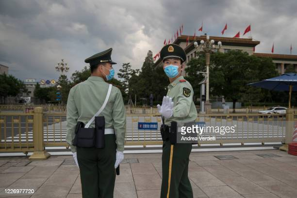 Soldiers of the People's Liberation Army stop the photojournalist from shooting in Tiananmen Square at the end of the Second Plenary Meeting of the...