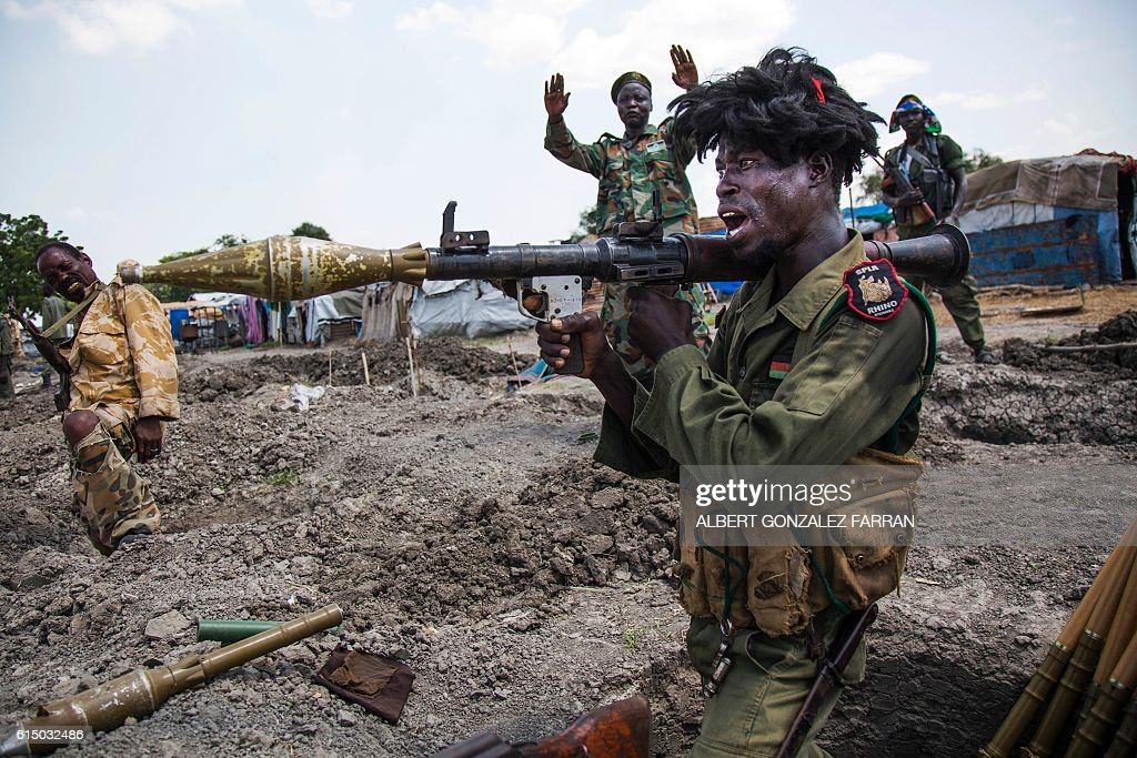 TOPSHOT - soldiers of the Sudan People Liberation Army (SPLA) celebrate while standing in trenches in Lelo, outside Malakal, northern South Sudan, on October 16, 2016. Heavy fighting broke out on Ocotober 14 between SPLA (Government) and opposition forces in Wajwok and Lalo villages, outside Malakal. SPLA commanders claim they succeeded to keep their positions and assure their forces just responded 'on self defence'. / AFP / Albert Gonzalez Farran