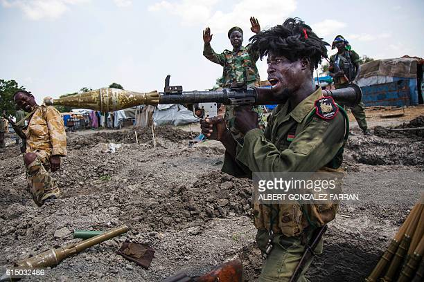 TOPSHOT soldiers of the Sudan People Liberation Army celebrate while standing in trenches in Lelo outside Malakal northern South Sudan on October 16...