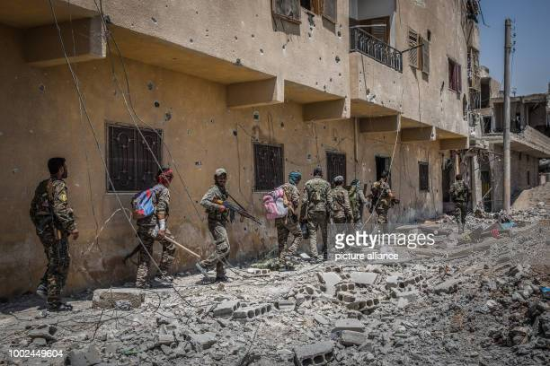 Soldiers of the Syrian Democratic Forces move through debris at the front line in the Al Dariya neighborhood in western Raqqa, Syria, 24 July 2017. A...