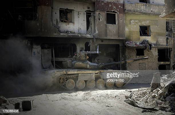 Soldiers of the Syrian government forces patrol on a tank in a devastated street on July 31 2013 in the district of alKhalidiyah in the central...