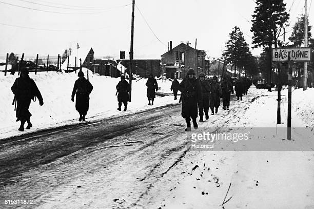 Soldiers of the US 101st Division march out of Bastogne Belgium on a snowy street during or just after the siege laid on the town in the Battle of...