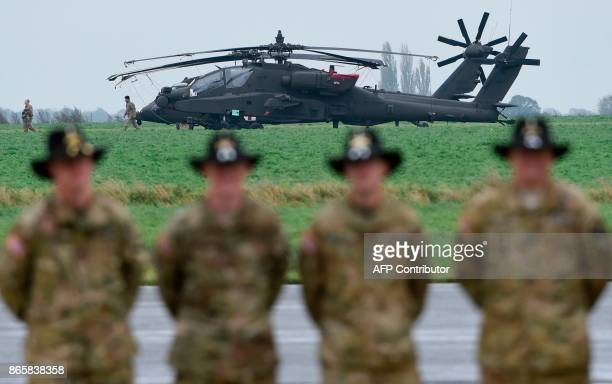 Soldiers of the US Army 1st Cavalry Brigade 1st Cavalry Division stand in front of a Boeing AH64 Apache helicopter on the tarmac at Shape Airfield at...