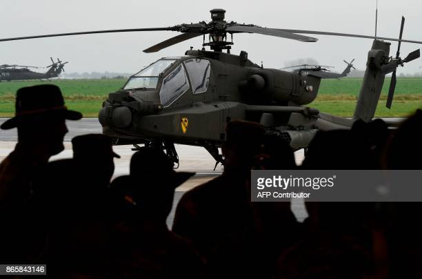 Soldiers of the US Army 1st Cavalry Brigade 1st Cavalry Division stand in front of an AH64 Apache helicopter on the tarmac at Shape Airfield at...