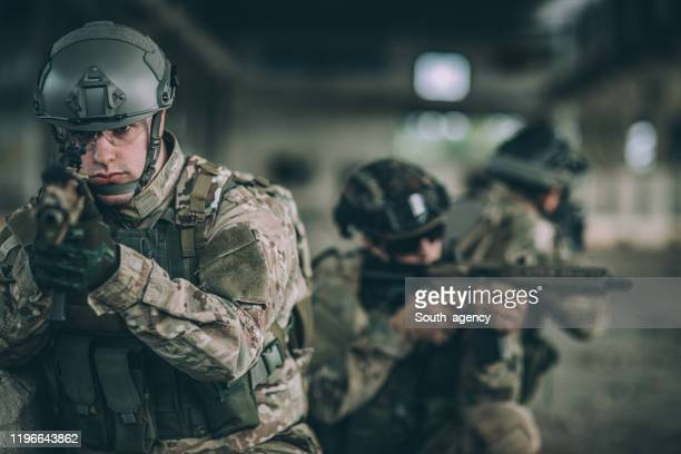 soldiers on a mission in abandoned warehouse - battlefield stock pictures, royalty-free photos & images