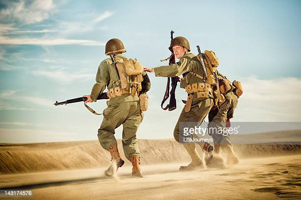 wwii soldiers  - on patrol in stormy desert sands - boots rifle helmet stock pictures, royalty-free photos & images