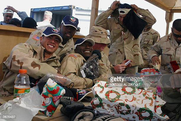 US soldiers open their Christmas presents at camp Victoria 100 Kms north of Kuwait City 21 December 2003 Kuwaiti companies presented over 20000 bags...