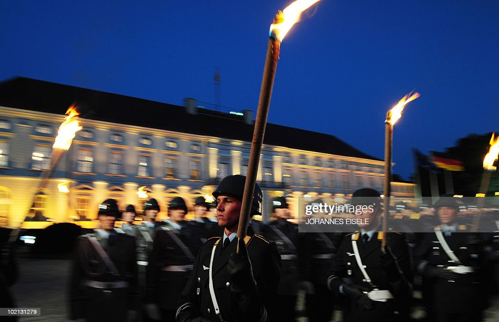 Soldiers parade with torches during the military tattoo honouring outgoing German President Horst Koehler (not pictured) in the courtyard of Bellevue Palace in Berlin on late June 15, 2010. Koehler, 67, resigned on May 31, 2010 following criticism of comments he had made about Germany's mission in Afghanistan.