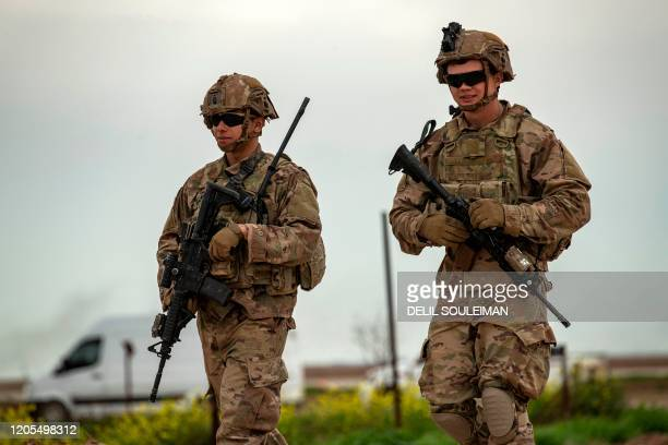 US soldiers part of the international military intervention against the Islamic State group walk at a military base in Rumaylan in Syria's...