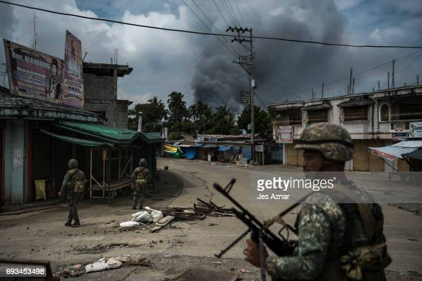 Soldiers patrol a street as smoke billows from a fire caused by heavy gunfights and aerial strikes on June 6 2017 in Marawi city Philippines Now...