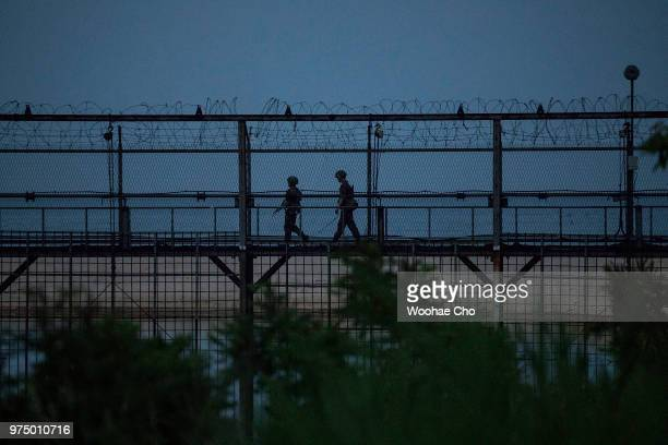 Soldiers patrol along the fence in the beach on June 7, 2018 in Hyeonnae, South Korea. Around 2,700 South Korean villagers live under tight military...