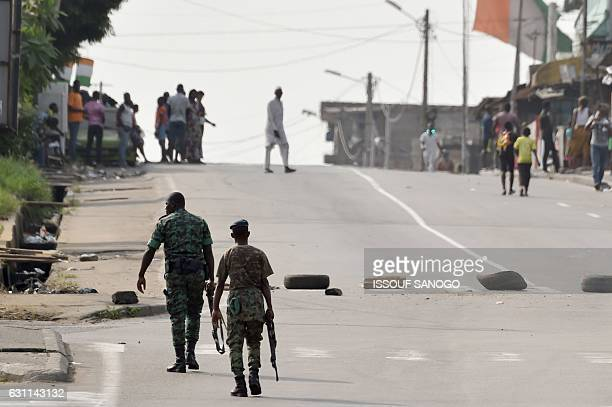 Soldiers patrol near tyres blocking the road in the Plateau business district of Abidjan on January 7 2017 as shots were heard inside a military camp...