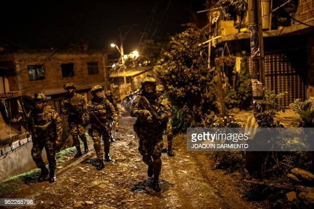 TOPSHOT Soldiers patrol the alleys of the Comuna 13 neighbourhood in Medellin Antioquia Department Colombia on April 27 2018 The Comuna 13...