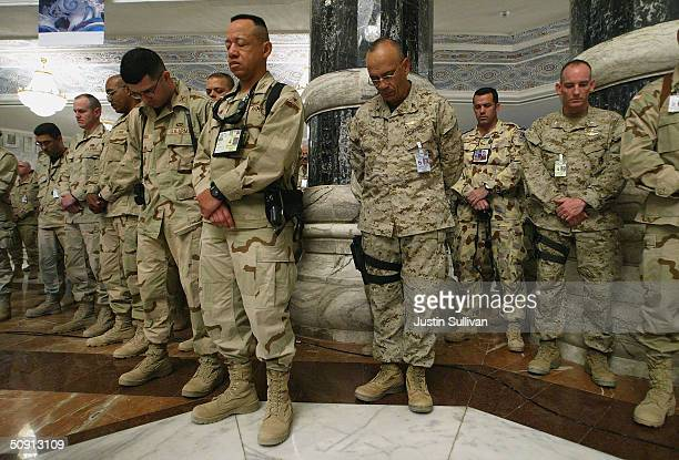 BAGHDAD IRAQ MAY 31 Soldiers pause for a moment of silence during a Memorial Day ceremony May 31 2004 at Camp Victory in Baghdad Iraq Soldiers...