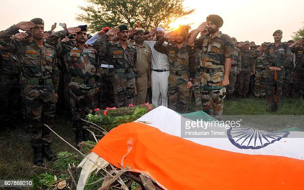 Soldiers paying tribute to Martyr Ravi Paul during his last rites with full military honour at his village Sarwah on September 19 2016 in Samba...