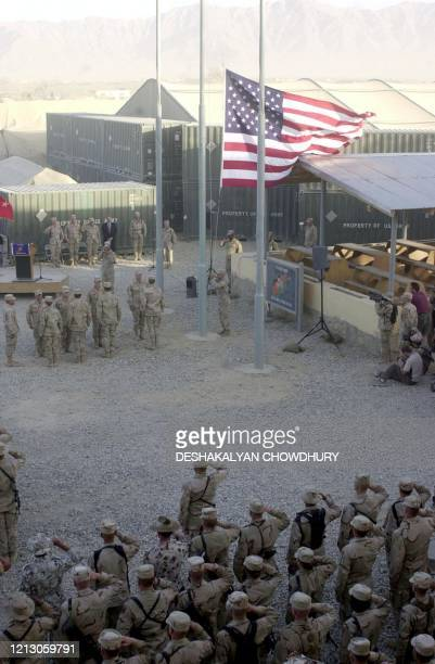Soldiers perform a flag lowering ceremony at the Bagram Air Base 11 September, 2002. The soldiers observed the ceremony to commemorate 11 September...