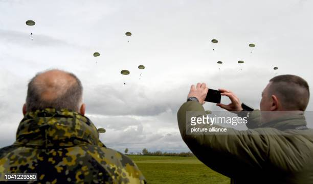 Soldiers photograph paratroopers jumping out of a Transall transport plane over Ahrenvioelfeld Germany 10 May 2017 Around 3500 German and Dutch...