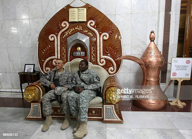US soldiers pose for a photo as they sit on a chair that belonged to executed Iraqi dictator Saddam Hussein at the former presidential palace which...