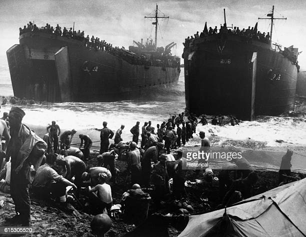 Soldiers pour from huge Coast Guardmanned landing craft onto a beach at Leyte Island in the Philippines during the invasion of October 1944 Their...