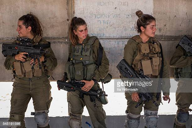 Soldiers prepare their rifles for practice at a shooting range on July 6 2016 in Nitzana IsraelThe first mixedsex Karakal combat battalion was formed...