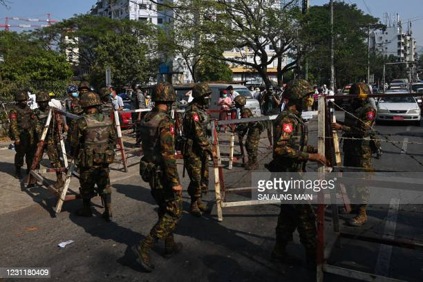 Soldiers prepare to block a road in front of the Central Bank of Myanmar in Yangon on February 15 as Myanmar's junta deployed extra troops around the...