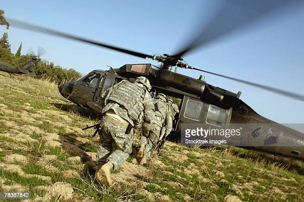 soldiers prepare to board a uh-60 black hawk helicopter. - hawk stock photos and pictures