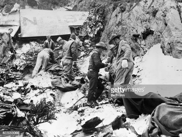 Soldiers prepare to lower the bodies of persons killed in the crash of a TWA airliner one of which was Carole Lombard Scattered below the rugged face...