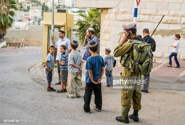 Soldiers protect settlers and their children in H2 zone, Hebron. Hebron is one of the most disputed cities of the West Bank. Hundreds of Israeli...