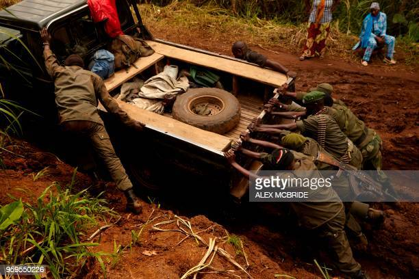 soldiers push their patrol vehicle out of heavy mud on the road between Kibirizi and Bwito in Ruthshuru territory of North Kivu on May 5 2018 The...
