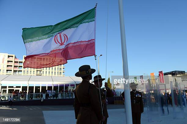 Soldiers raise the Iranian flag during a flagraising ceremony as members of the Iran Olympic delegation arrive at the Athletes' Village at the...
