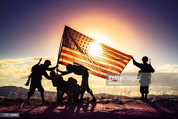 wwii soldiers raising the american flag at sunset - military flags stock photos and pictures